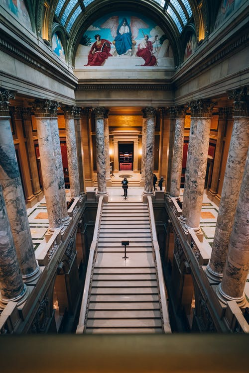 Aerial Photography of Man Standing on Top of Staircase Inside a Cathedral