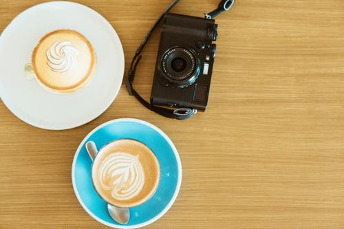 Black Camera And Two Coffee Cups With Saucers