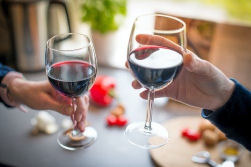 Close-up Photo of Two People Toasting With Red Wine