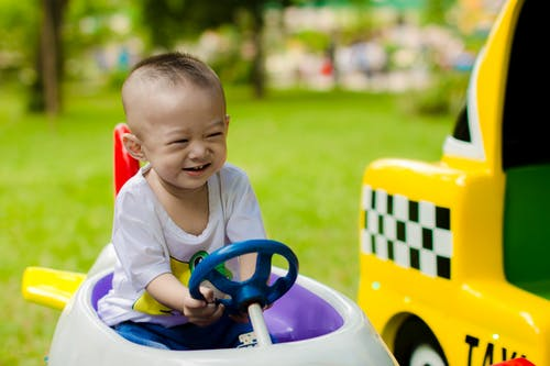 Boy Smiling While Riding Ride-on Toy