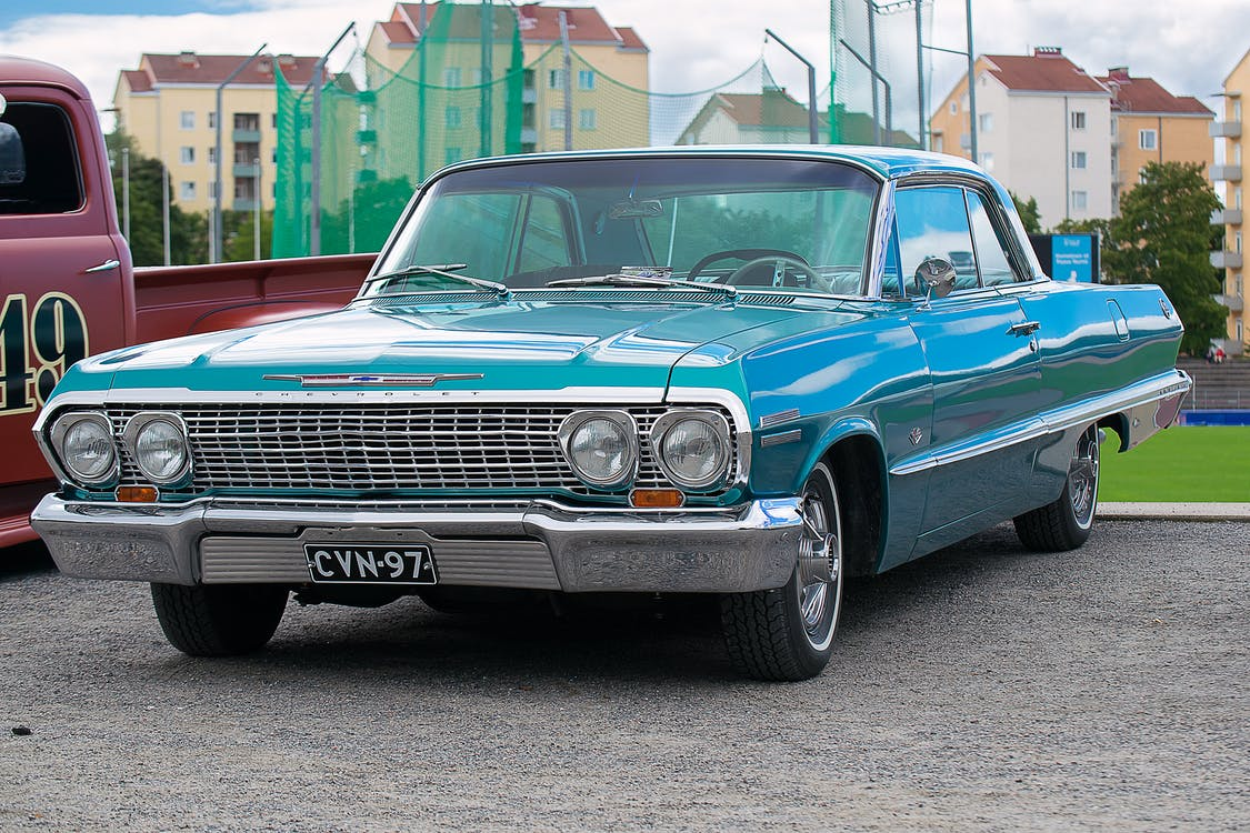 Classic Blue Coupe Parked Besides Red Pickup Truck