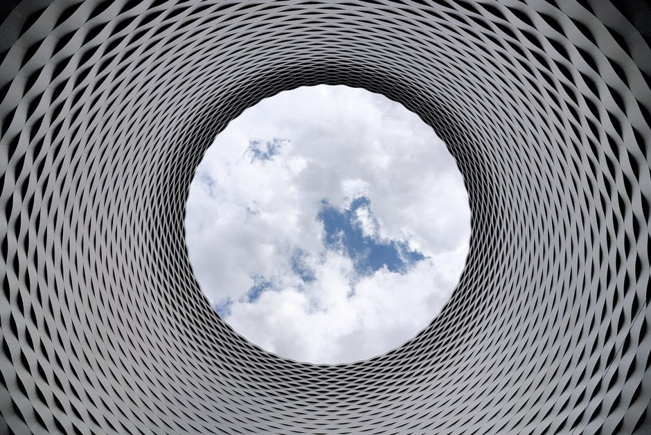 Low-angle Photography of Grey and Black Tunnel Overlooking White Cloudy and Blue Sky