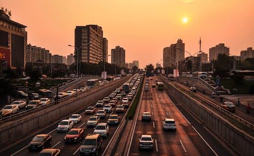 Gratis stockfoto met architectuur, auto's, autorijden, avond