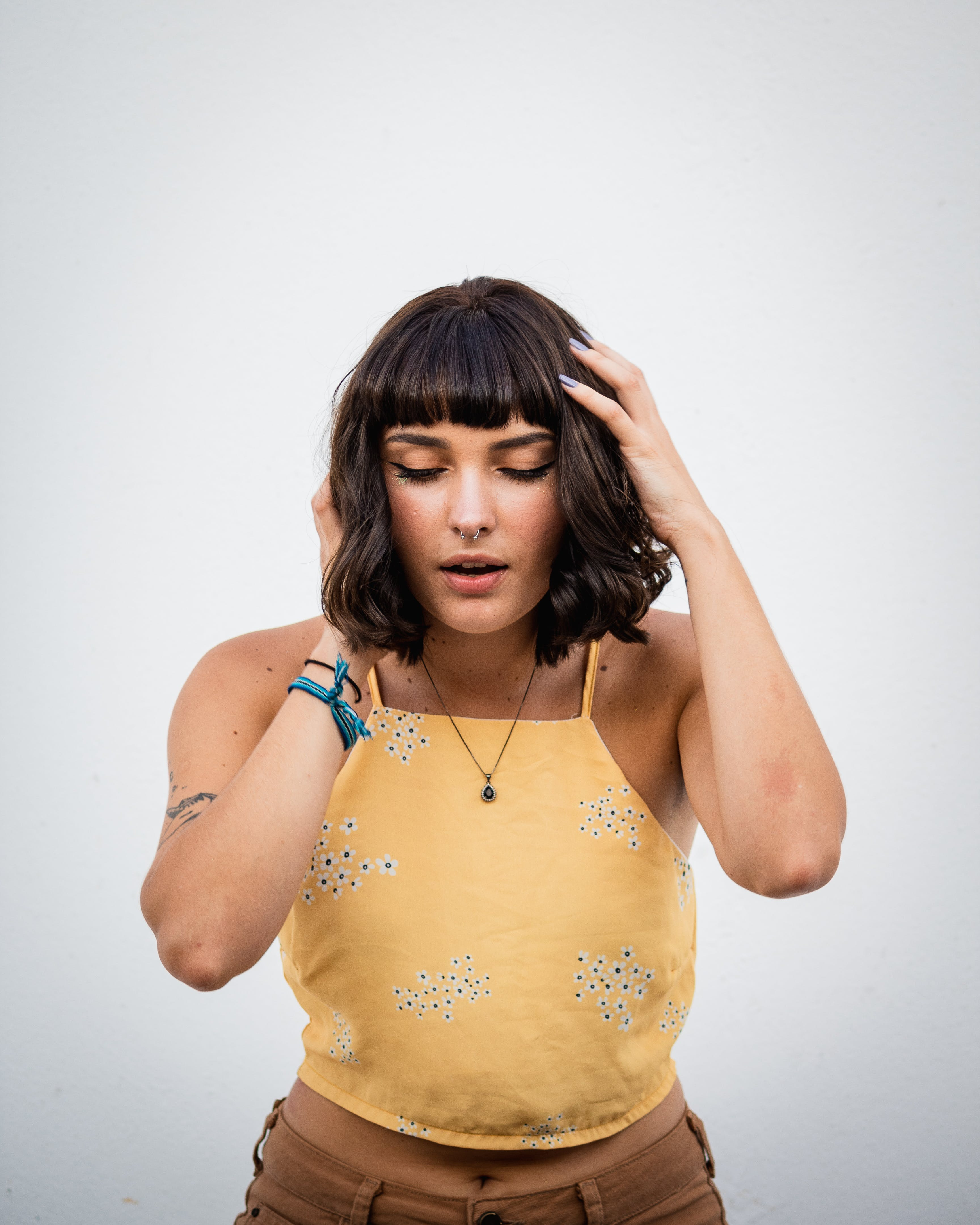 Photo of Woman in Yellow Crop Top Standing in Front of Wall With Her Eyes Closed