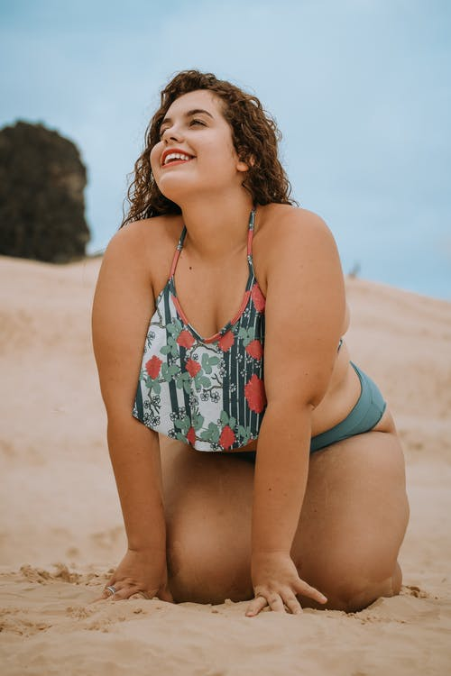 Woman Kneeling on Brown Sand While Smiling