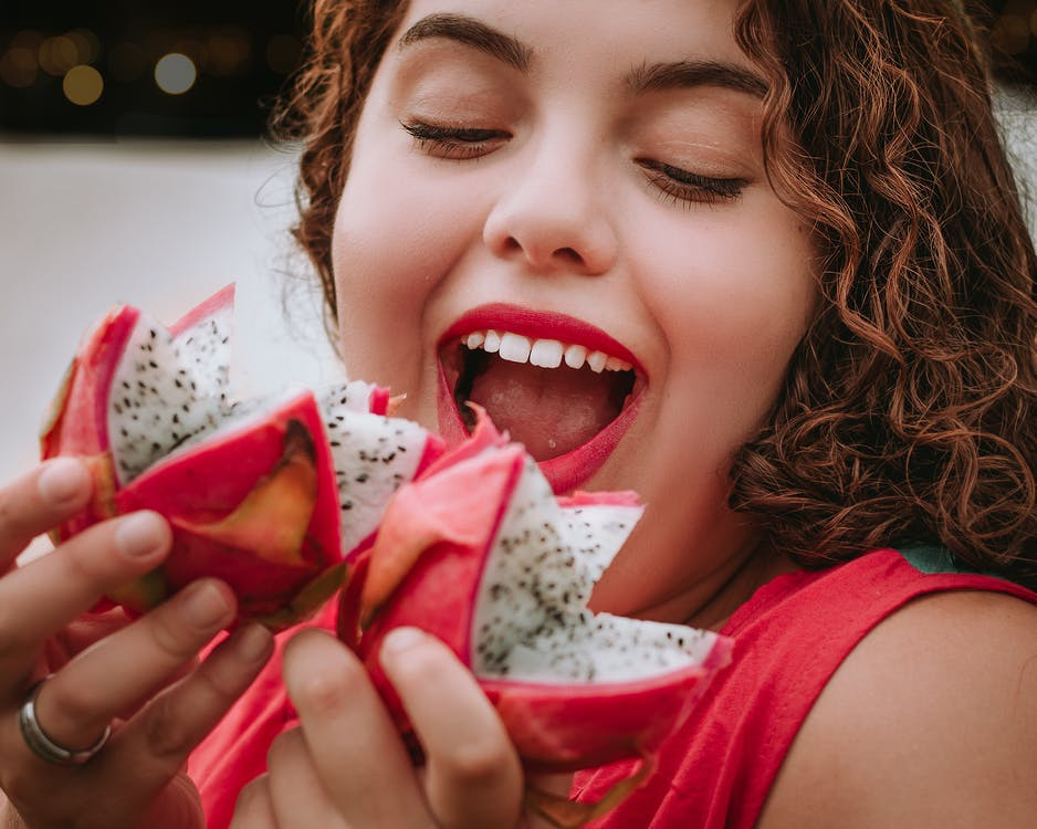 Smiling Woman Holding Dragon Fruits