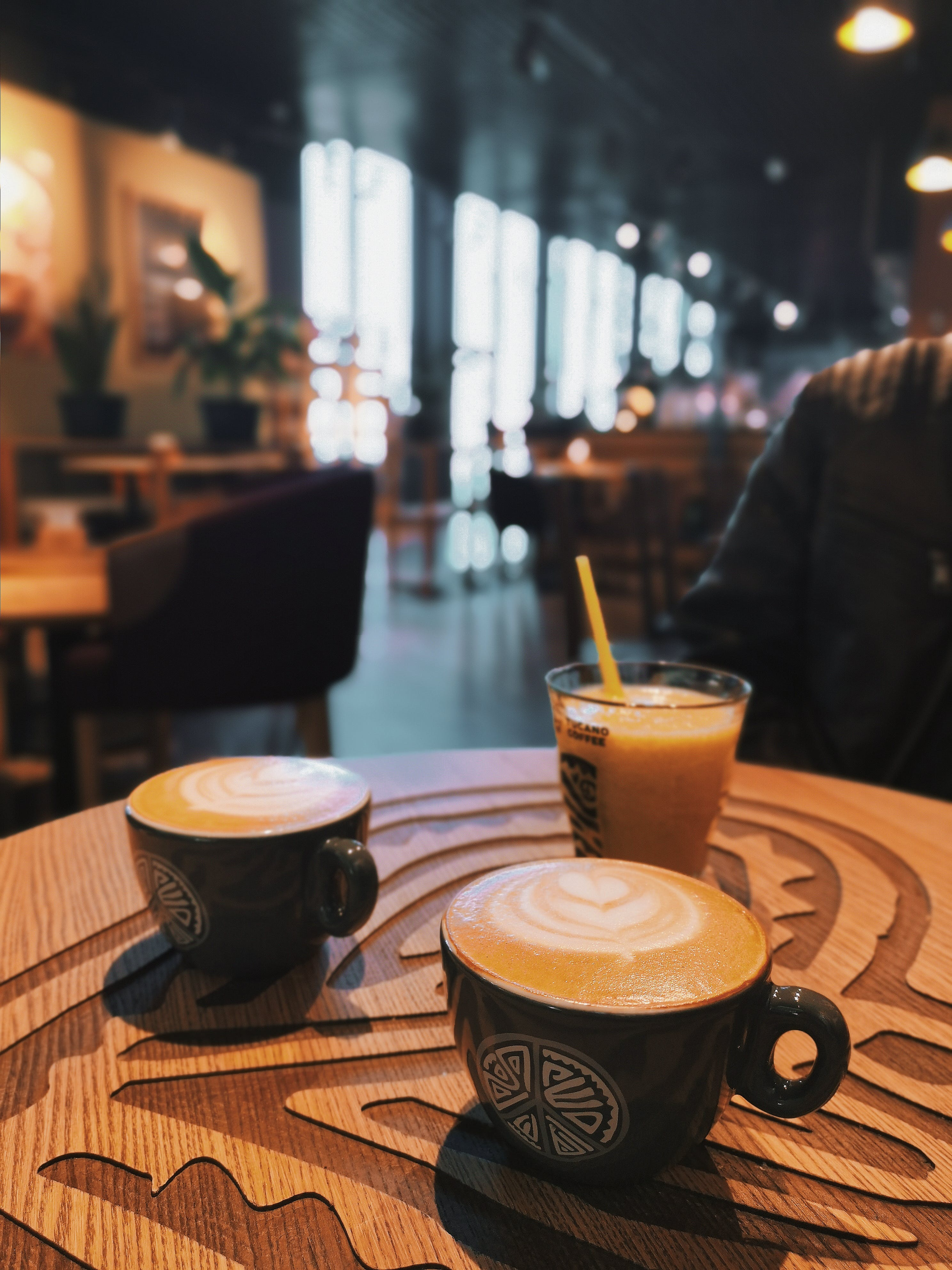 Two Cappuccino Near Ice Cold Drink on Table and Person Sitting Beside Brown Wooden Table