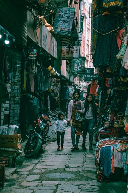 People on Pathway Between Stores