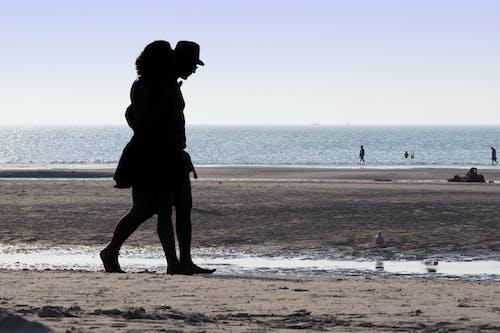 Man and Woman Walking at Beach