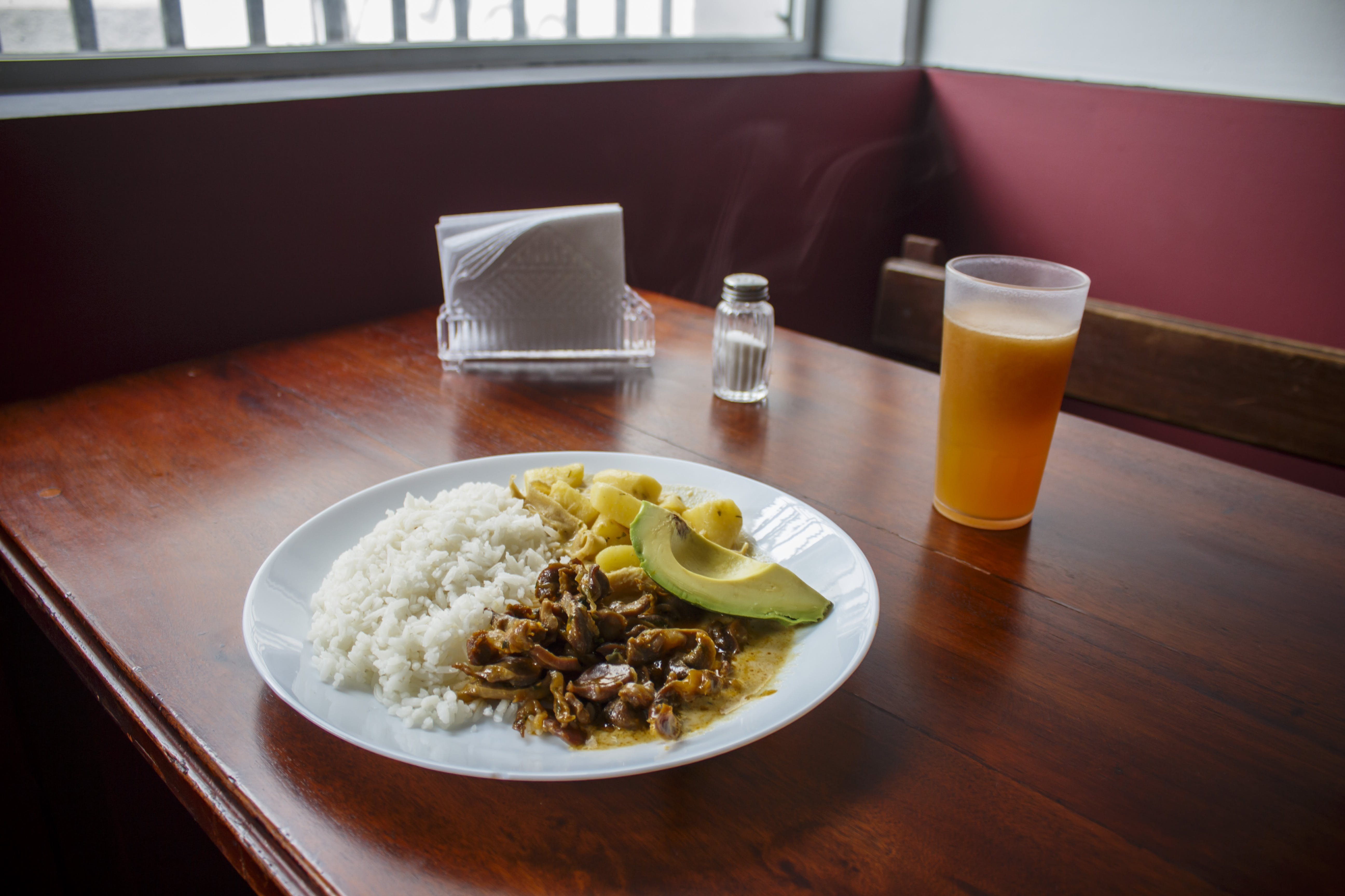 Plate of Cooked Rice With Cooked Beef Beside of Cup of Juice