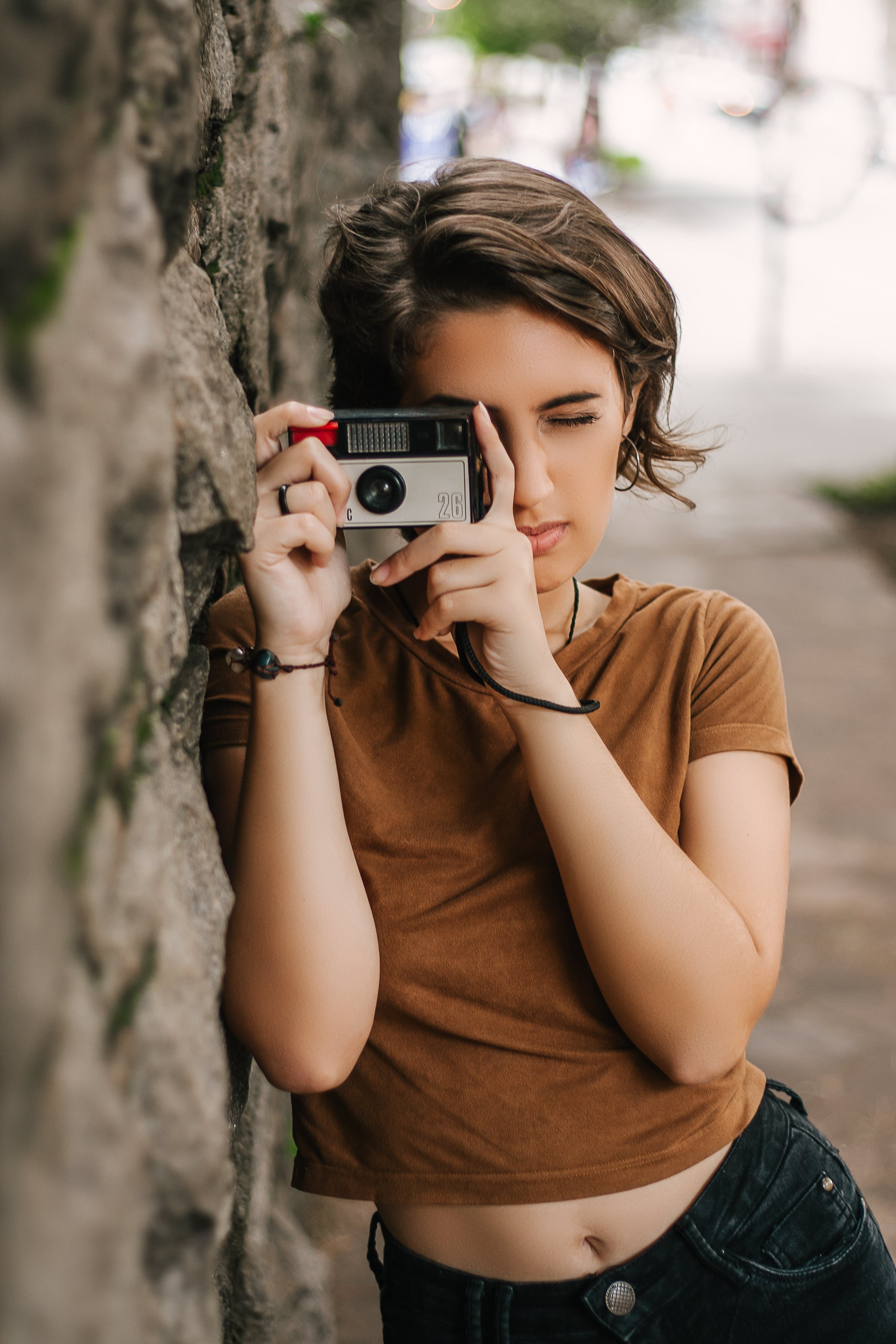 Woman Taking Photo While Leaning on Wall