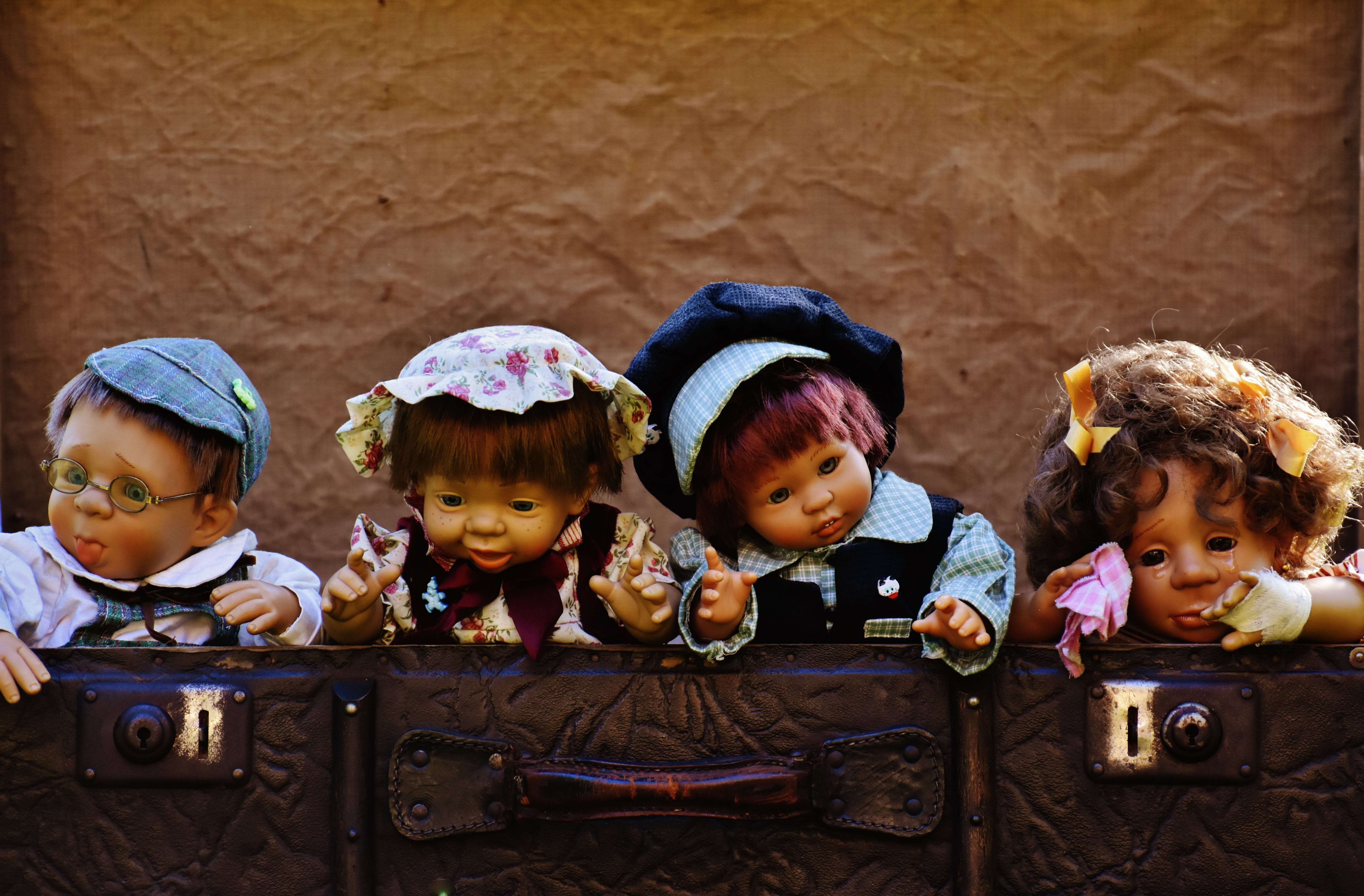 Four Dolls Near Brown Leather Bags