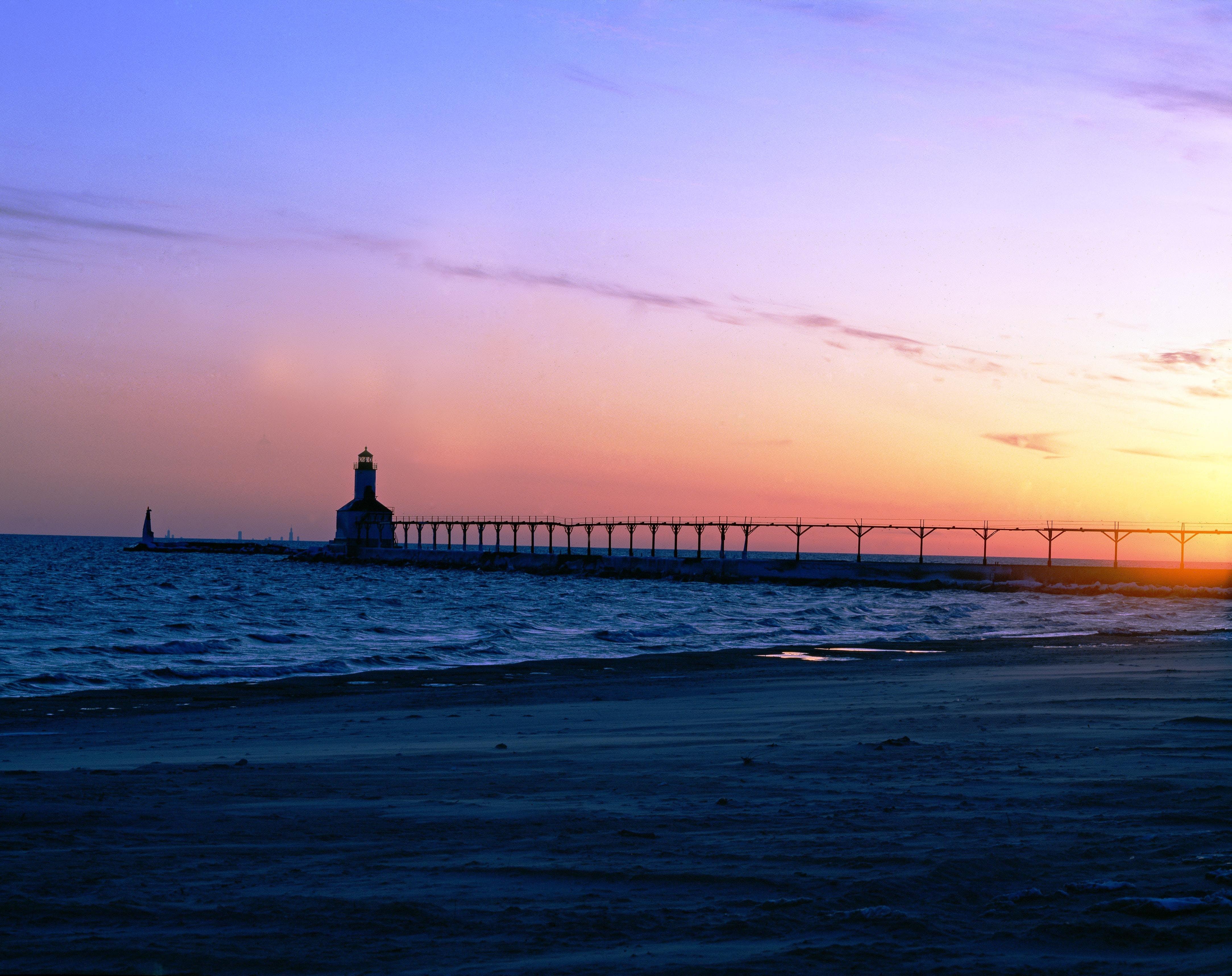Silhouette of Gray Steel Bridge on Sea Shore during Sunset