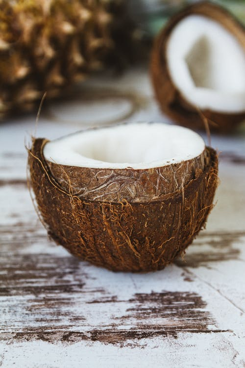 dừa bổ đôi để trên mặt bàn gỗ vệt trắng
