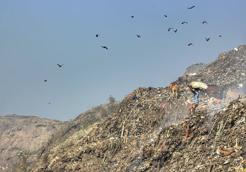 Distant man standing on hill with garbage dump against blue sky and scavengers soaring over trash in mountainous area in nature