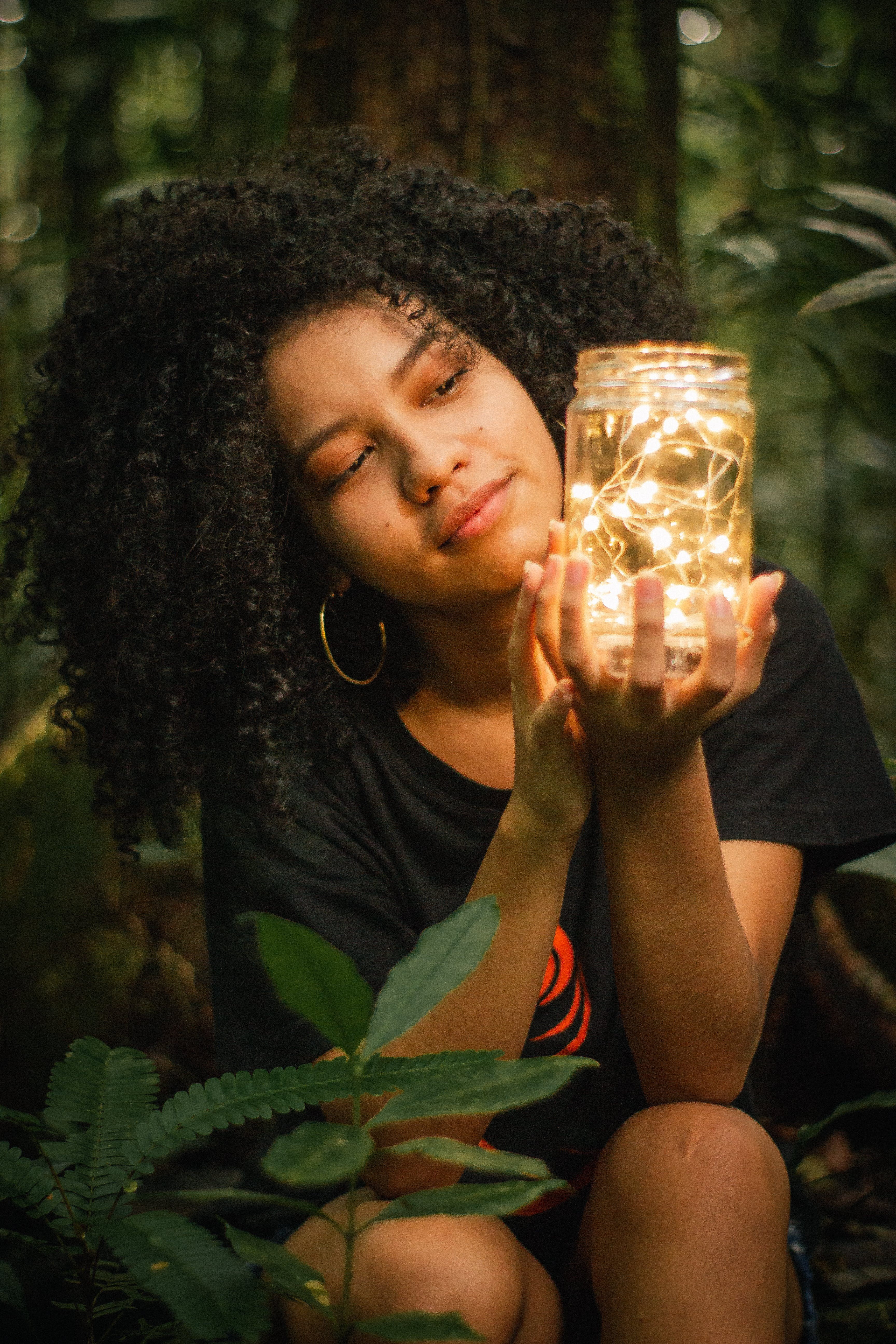 Woman Holding Clear Glass Jar Lamp Near Green-leafed Plant