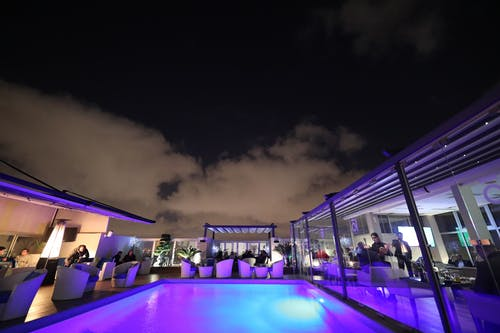 Swimming Pool Surrounded With Tables and Chairs at Night