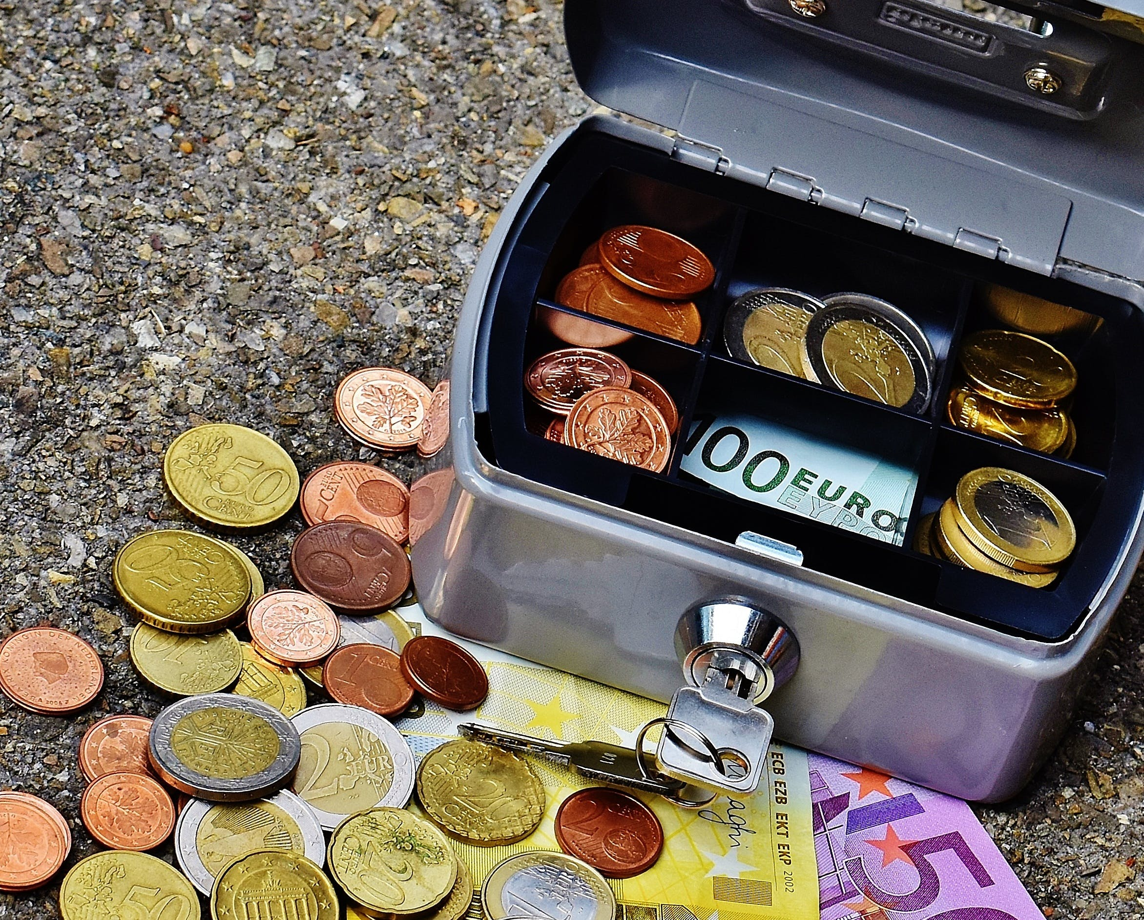 Open Gray Cash Box Beside Scatterd Coins