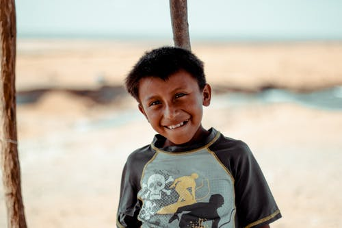Photo of Smiling Boy Leaning on Wooden Pole