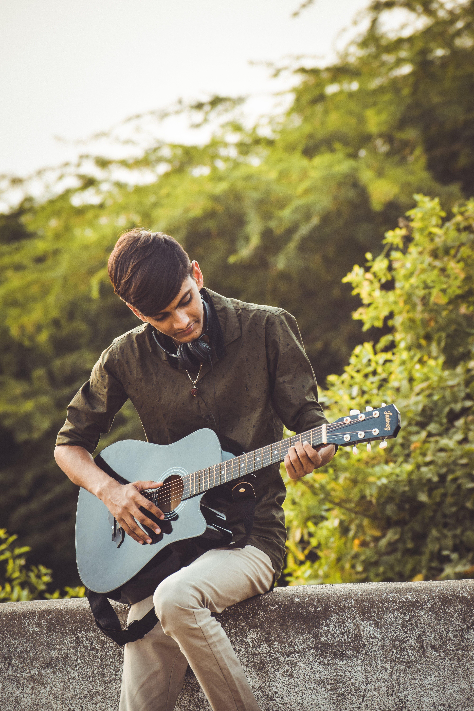 Man Playing Guitar Near Trees