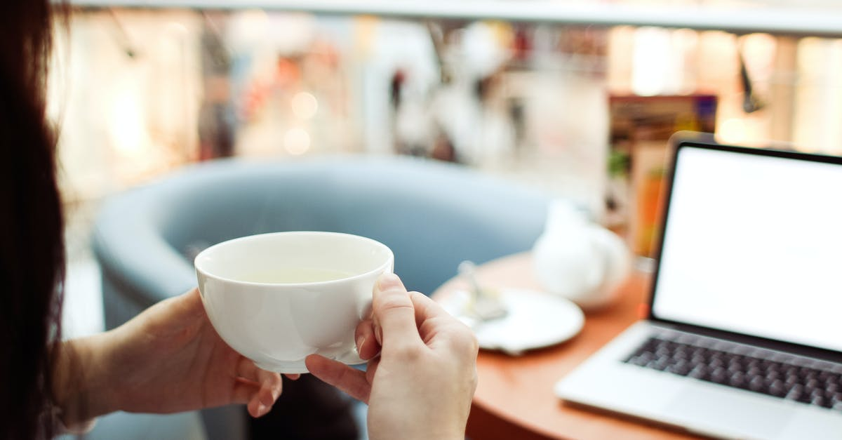Person Holding White Ceramic Teacup in Front of a Macbook Pro