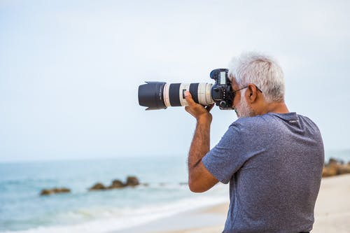 Man Taking Photo of Sea