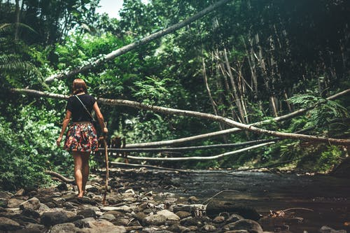 Woman Walking Beside River Holding Cane