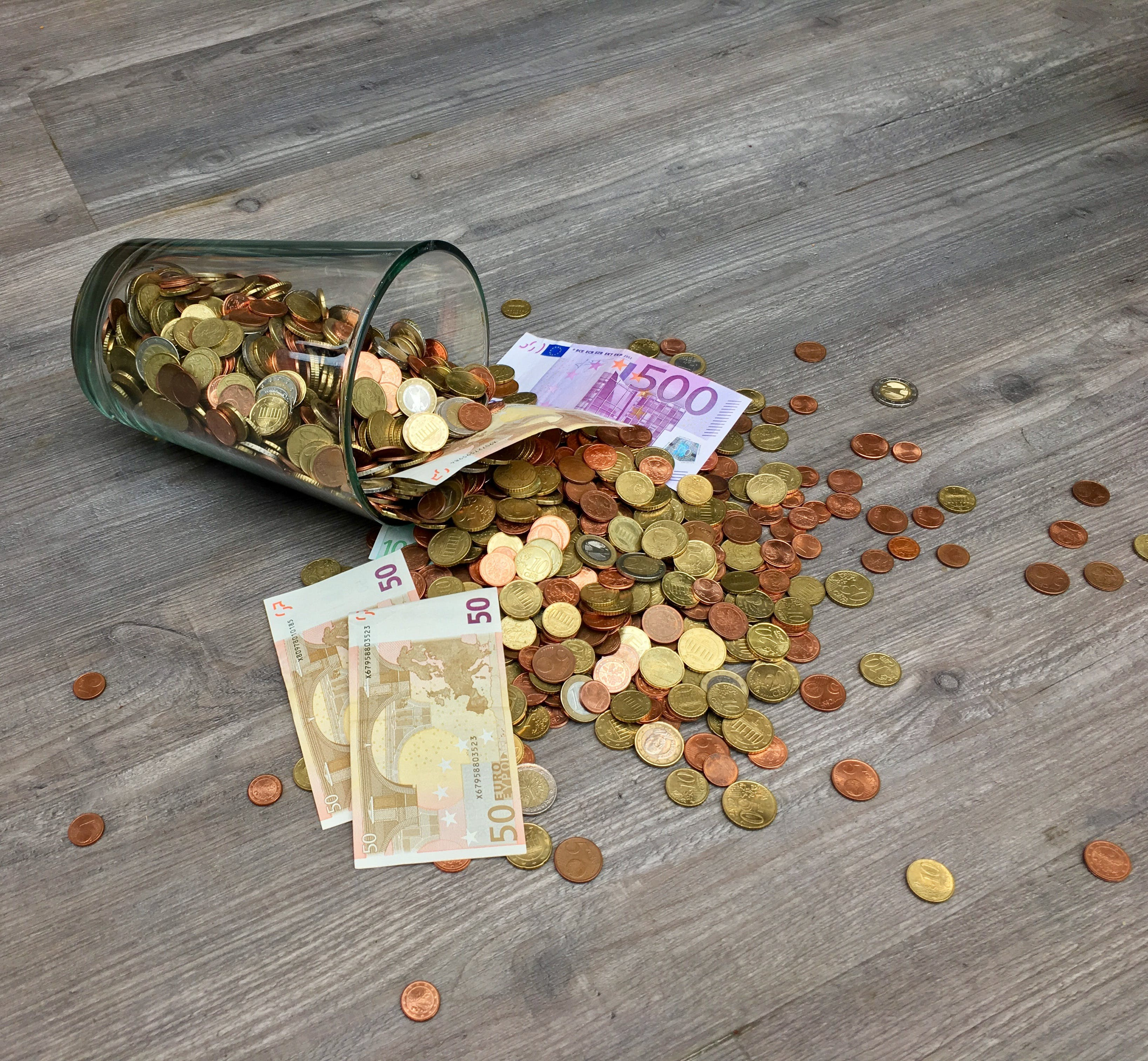 Coins and Banknotes Scattered on Gray Wooden Surface