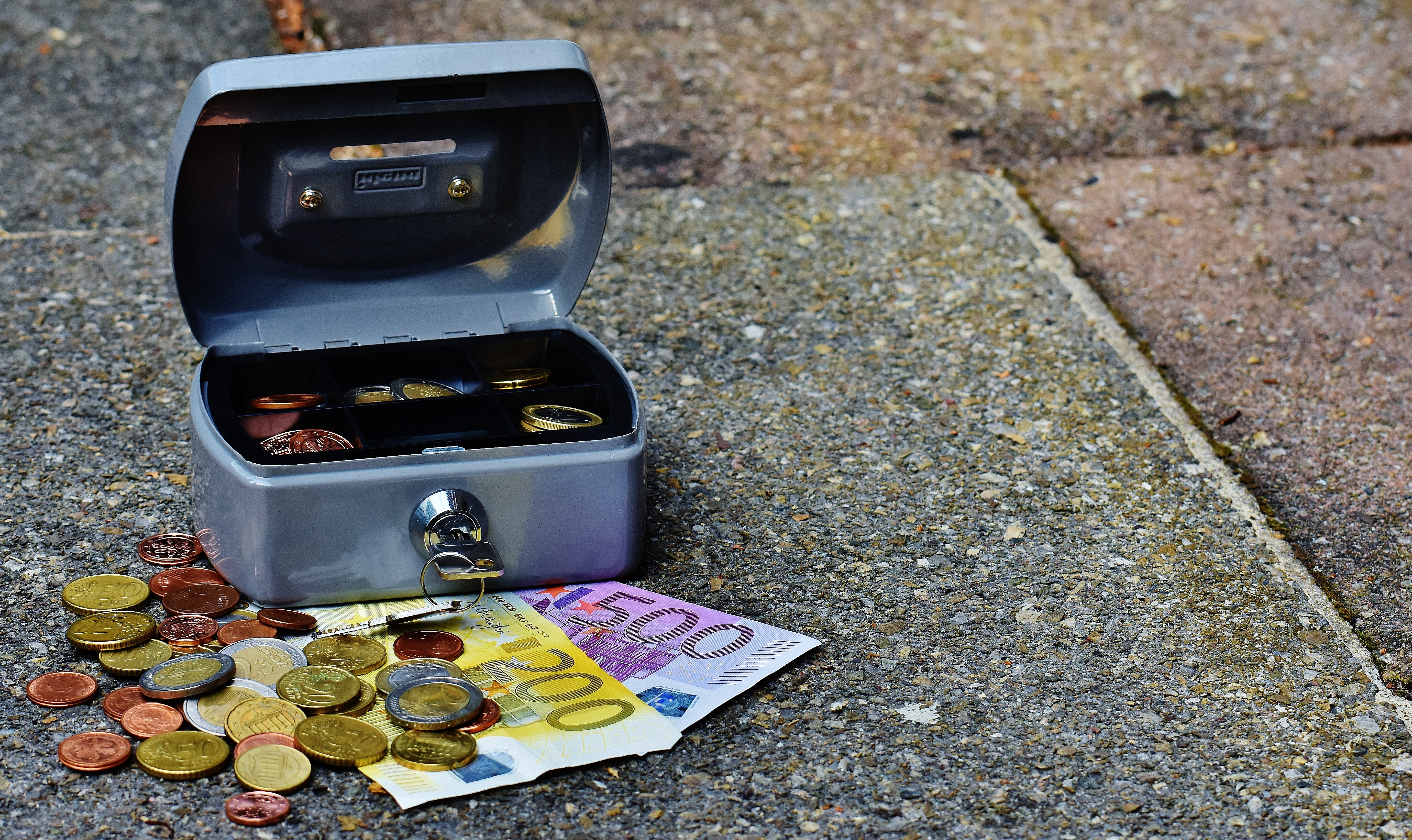 Gray Storage Box With Coins and Banknotes on Pavement