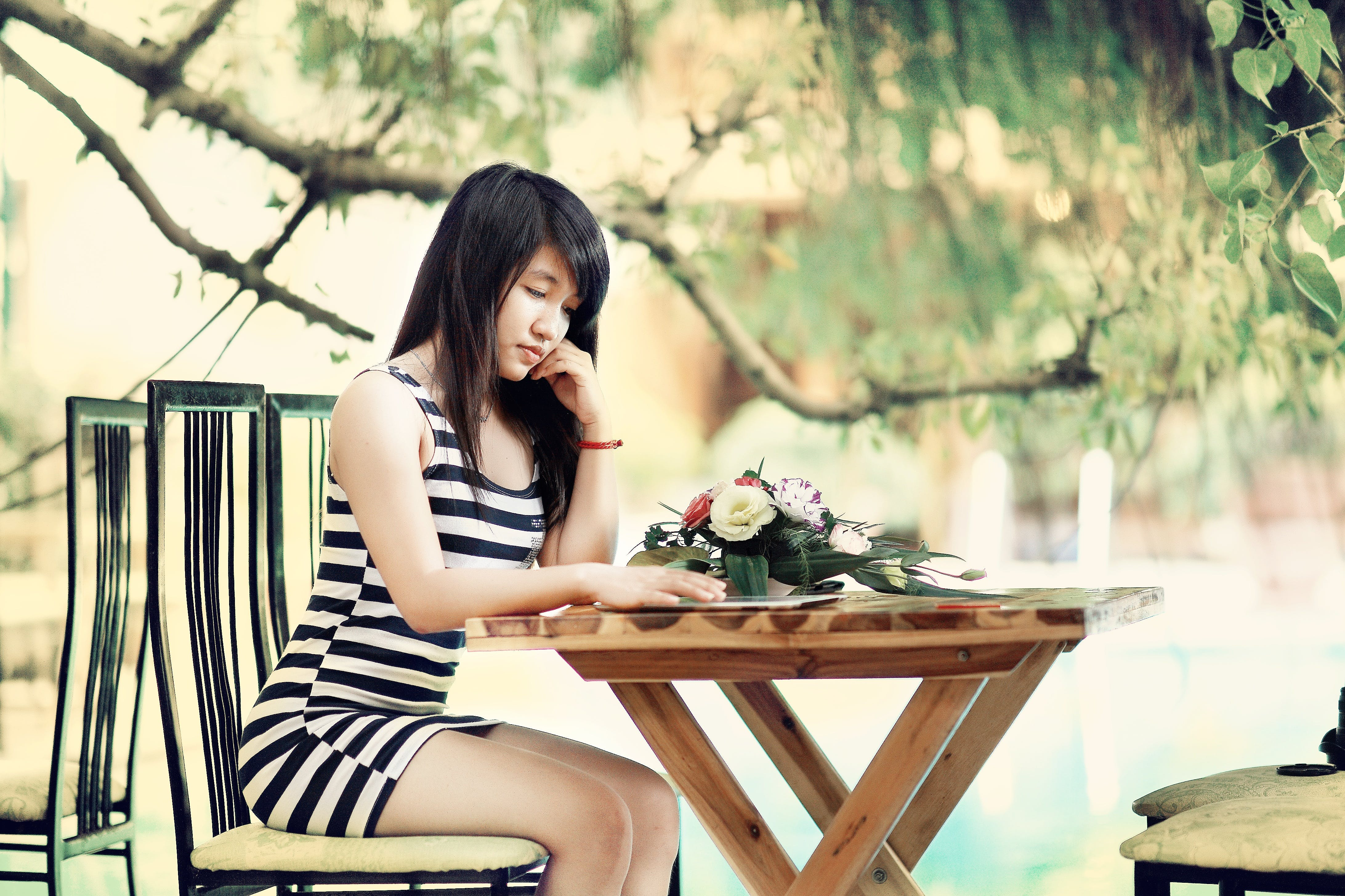 Woman Wearing Stripe Tank Bodycon Dress Sitting on Chair Leaning on Table