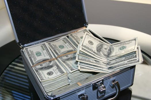 Piles of U.s. Dollar Bills on Silver and White Suitcase