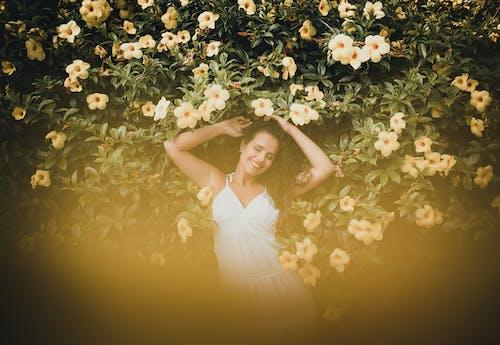 Woman Wearing White Dress Lying on Yellow Flowers