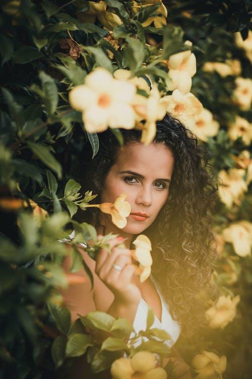 Femme Debout à Côté De Fleurs
