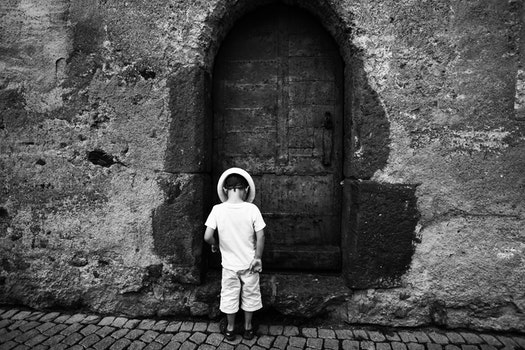 Grayscale Photo of Toddler Standing and Wearing Hat on the Ground