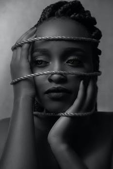 greyscale photo of woman holding face