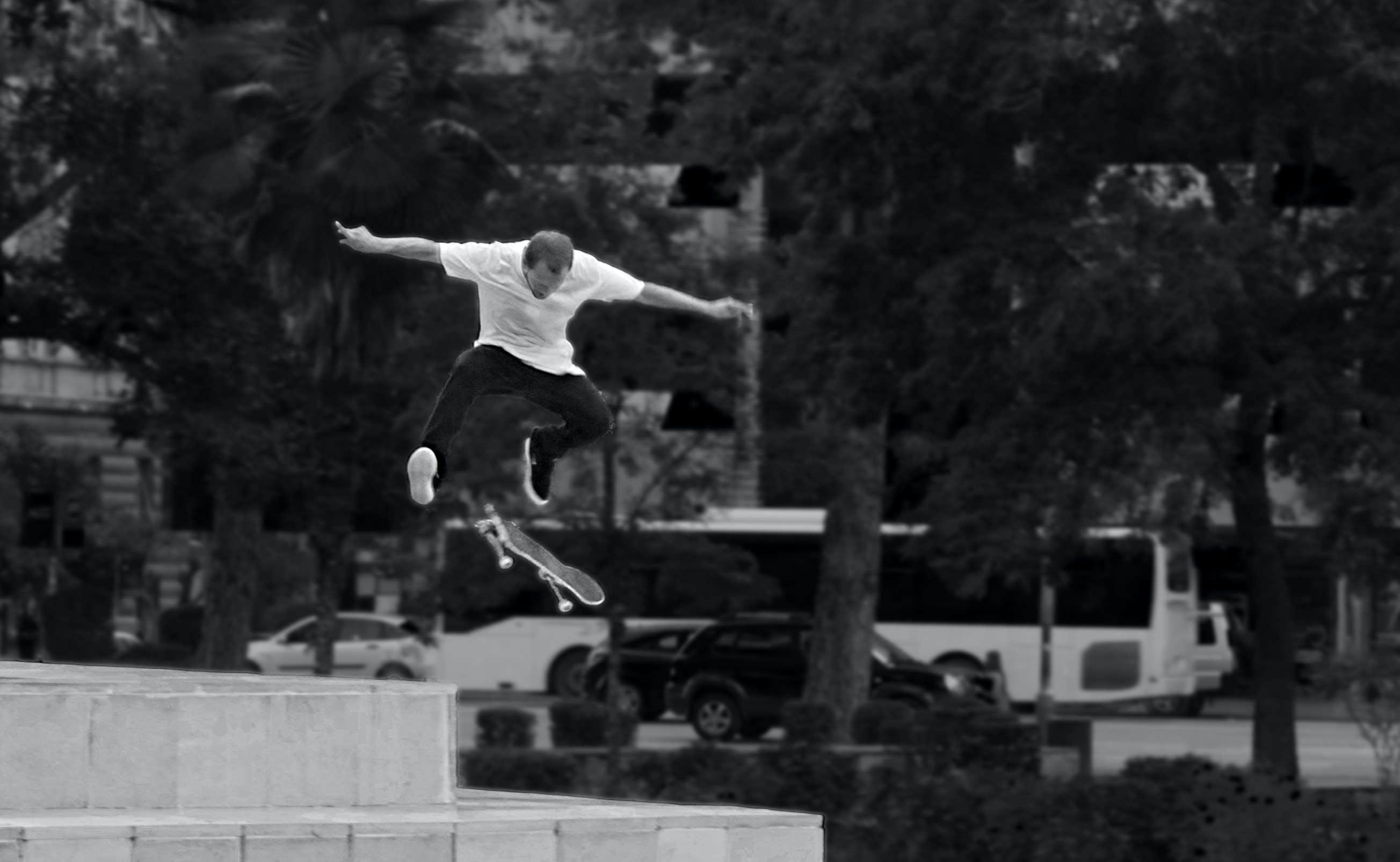 Man in White Shirt and Black Pants Playing Skateboard Near Green Tree during Daytime