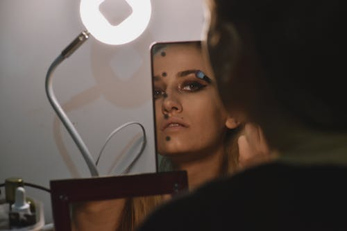 Person Wearing Make-up Looking at Mirror