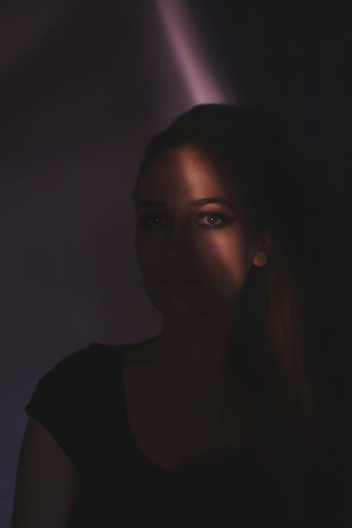 Woman in Black Shirt Inside Dark Room