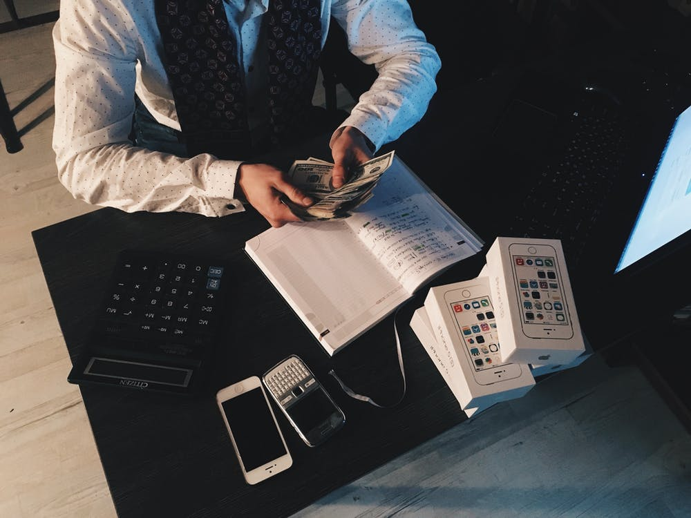 A man counting money on his desk. | Photo: Pexels
