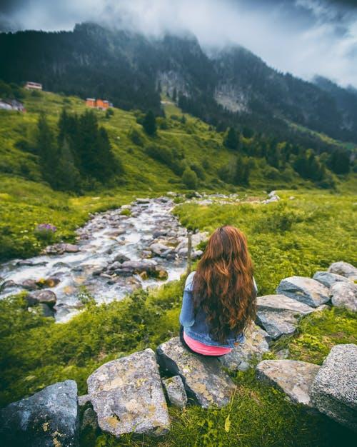 Woman in Denim Jacket Sitting on Rock Facing Mountain