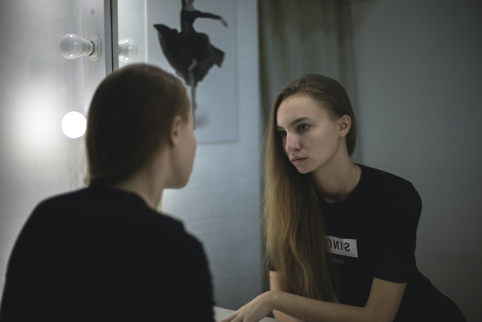 Woman in Black Shirt Facing Mirror