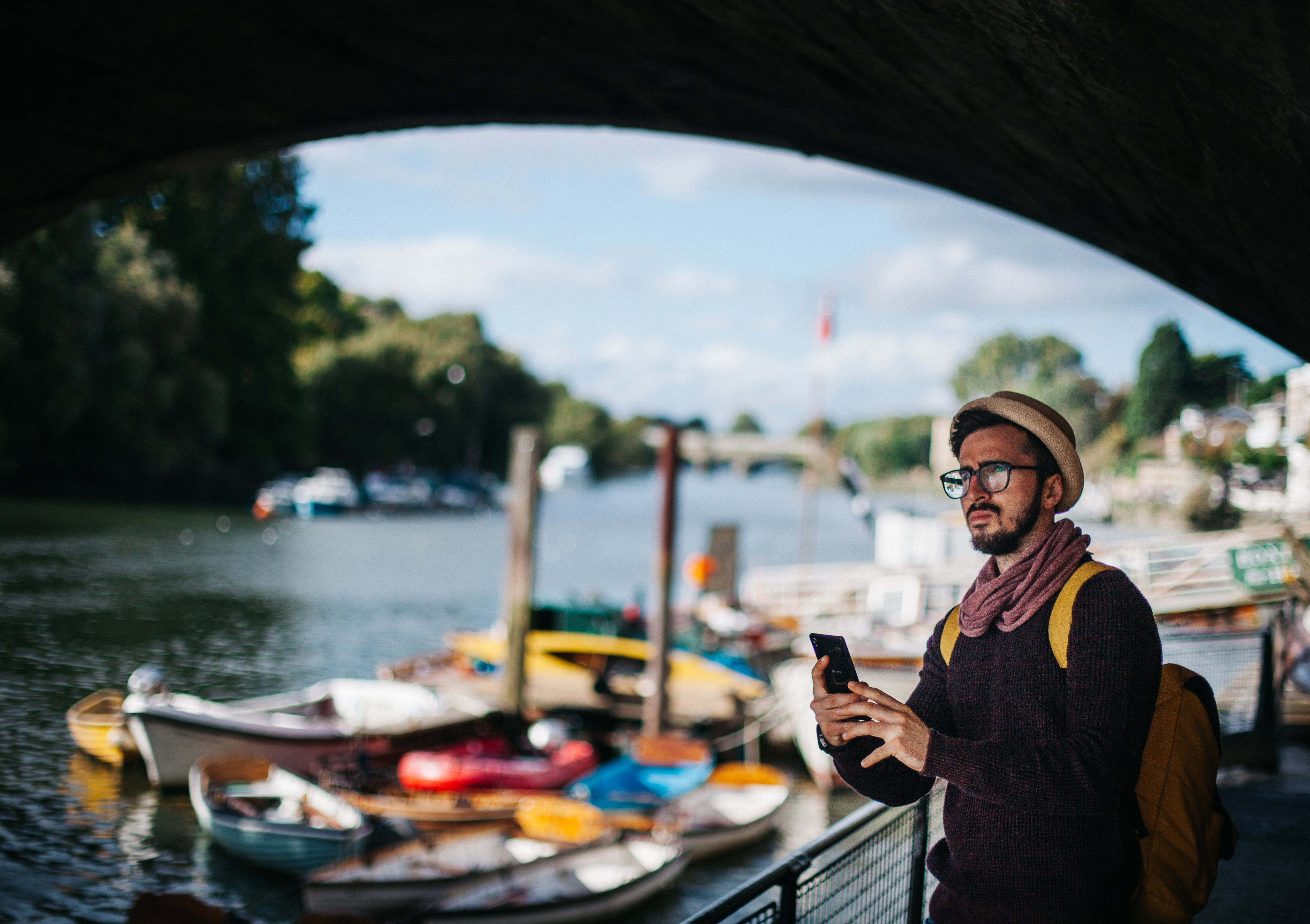 Man Holding Smartphone Near Boats