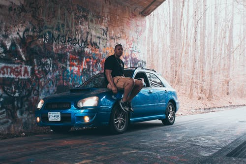 Man Sitting on Blue Vehicle