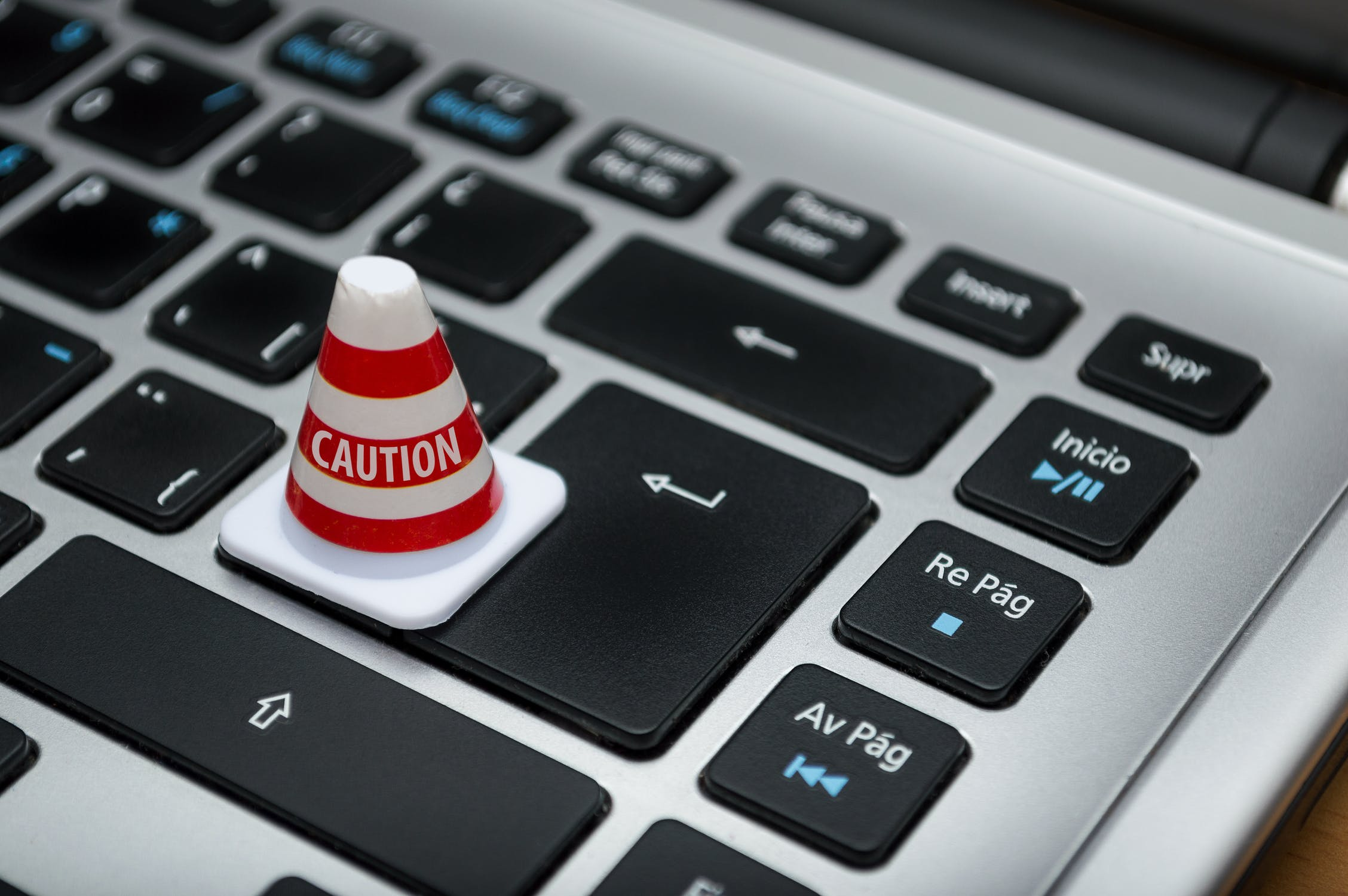 A small traffic cone reading 'Caution' on a computer keyboard