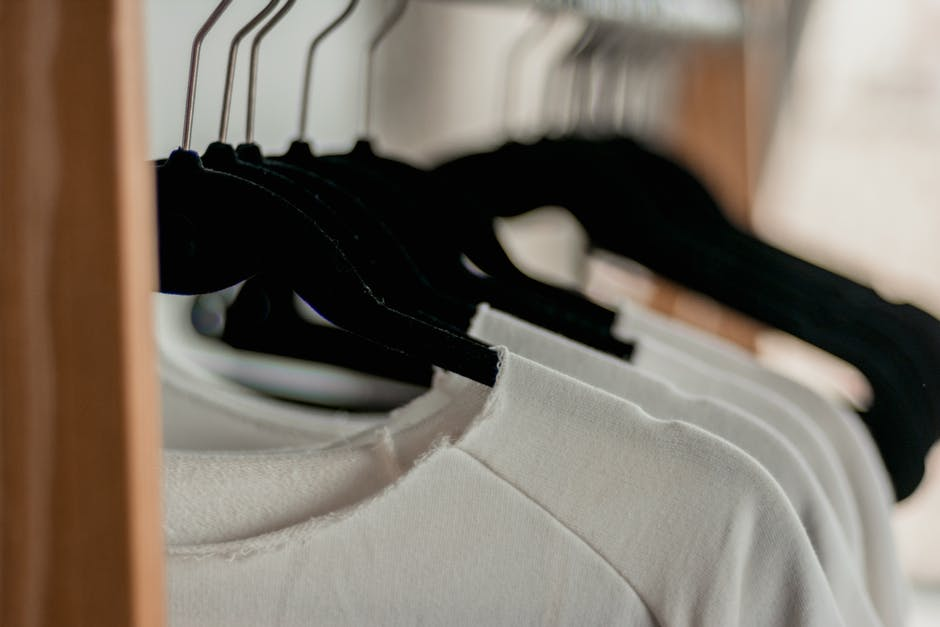 Hanged white shirts on black clothes hangers