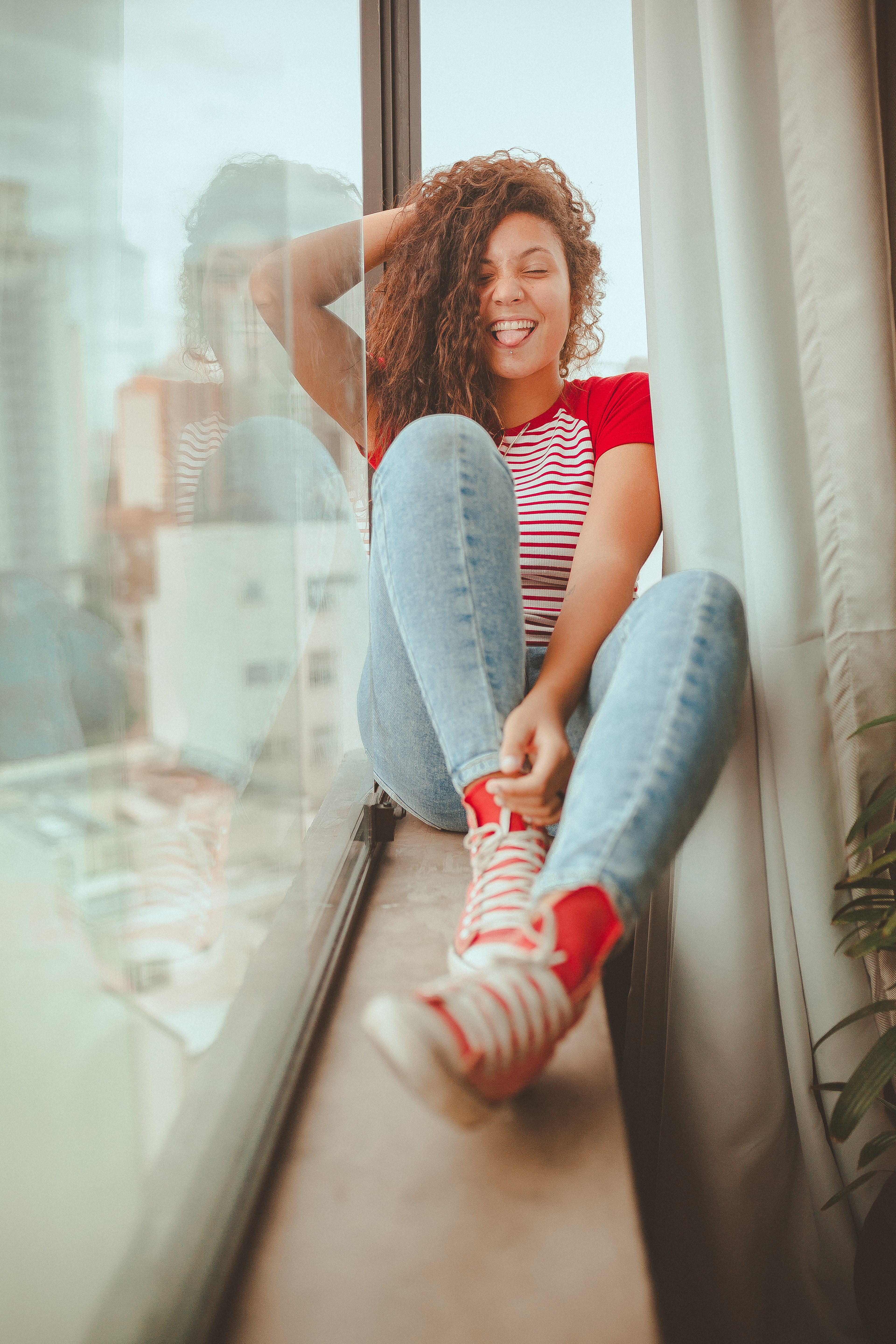 Smiling Woman Sitting Beside Glass Panel