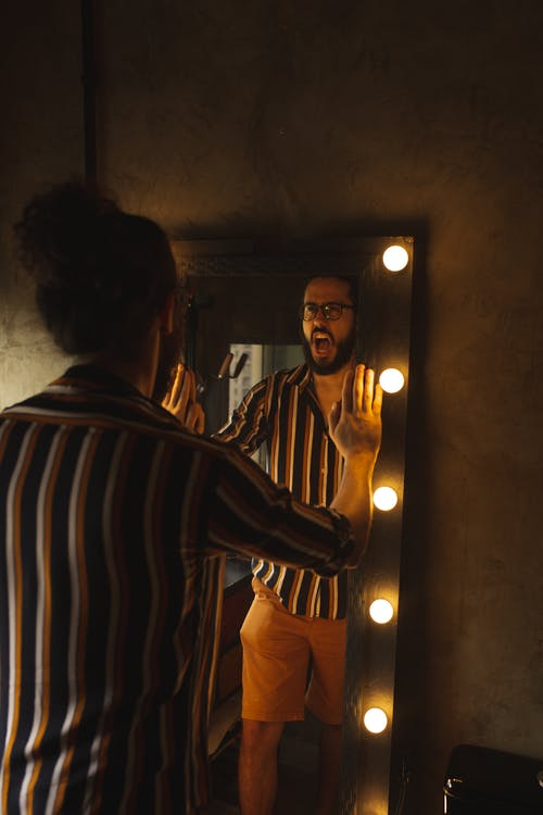 Man Opening His Mouth While Holding Mirror