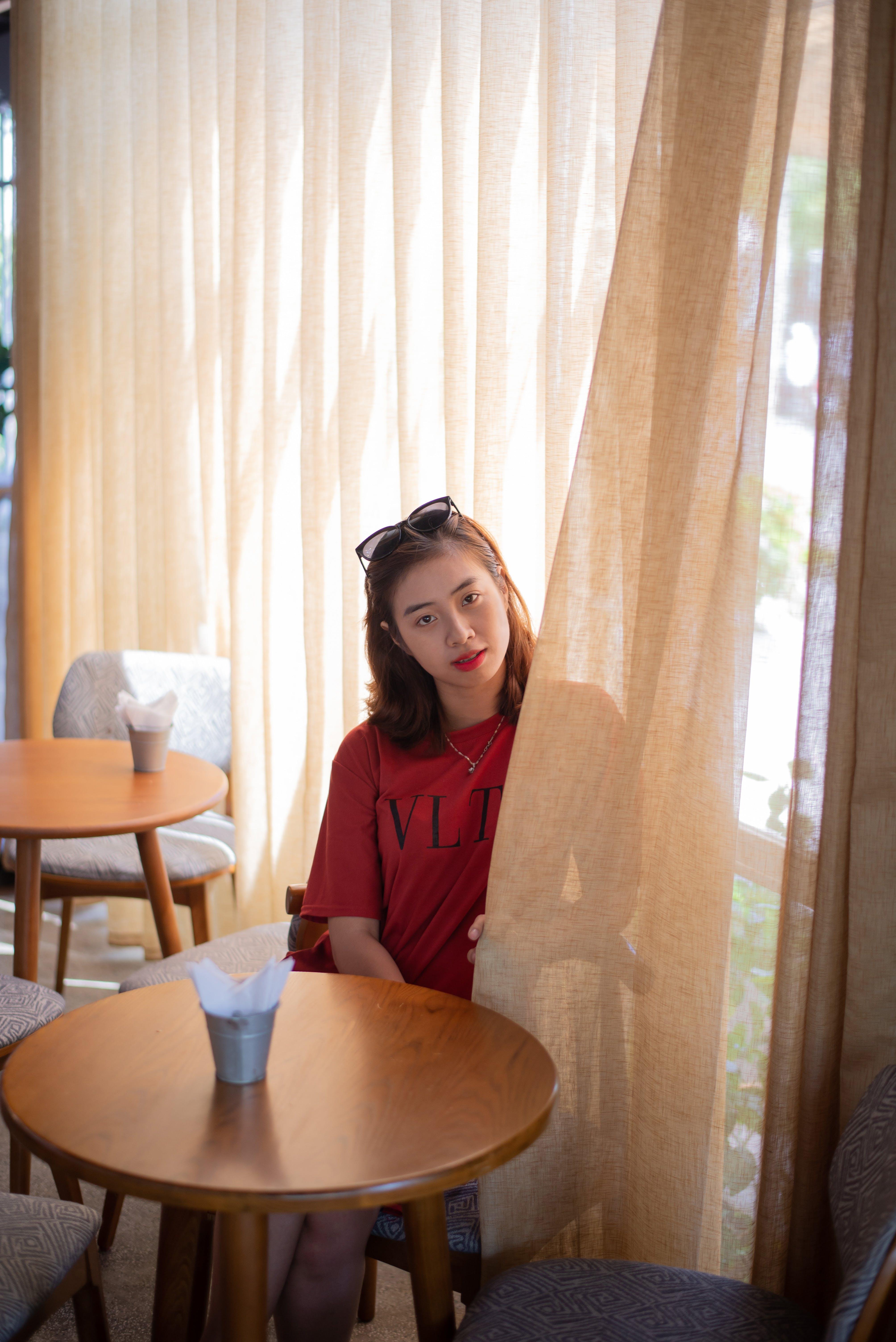 Woman Sitting Behind Curtain