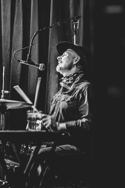 Greyscale Photo Of Man Playing Drums