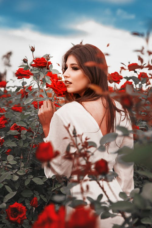 Photo Of Woman Wearing White Dress Surrounded By Red Roses